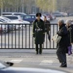 A paramilitary police official stands guard next to a fence in Beijing